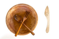 Wooden bowl with spoon, knife and fork on white background