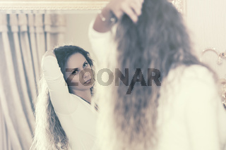 Beautiful fashion woman with long curly hairs looking in the mirror