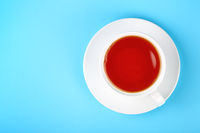 White cup of black or red fruit tea over blue