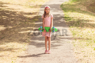 Girl with skate board on the park path
