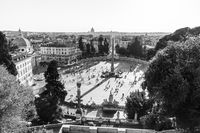Aerial view of people, sculptures, fountain and churches on Piazza del Popolo in Rome, Italy.