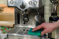 Barista cleaning coffee machine at cafe