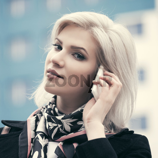 Young fashion business woman talking on cell phone walking in city street