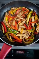 Prepares vegetables and chicken in frying pan
