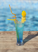 Glass with a bright blue lagoon cocktail on the table by the pool
