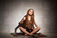 Woman with henna bodyart playin hapi drum view