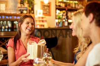 women giving present to friend at wine bar