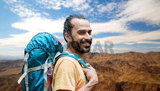 smiling man with backpack over grand canyon hills