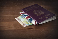Travel concept image: an italian passport over a union jack wallet and three euro banknotes on a wooden table