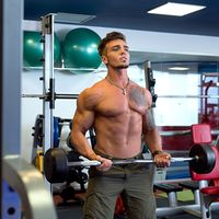 Handsome tattooed guy training with barbell