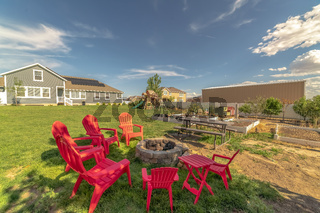 Backyard chairs around a stone fire pit adjacent to a picnic table with bench