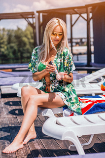 Sexy Woman Is Sitting On The Deck Chair At The Pool In Green Swinning Suit.