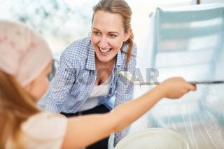 Lachende Mutter und Kind beim Malern