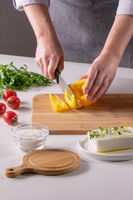 The girl's hand cuts pieces of pepper on a wooden board, cheese, and tomatoes on a white kitchen table. Preparation of salad