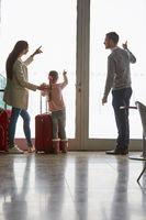 Familie mit Kind schaut aus dem Fenster im Flughafen