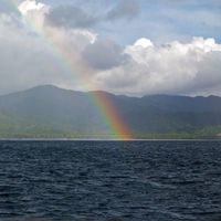 the rainbow from  ocean and island in background