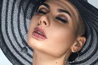 Studio portrait of beautiful young woman in sun hat