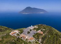 Aerial view of the church in the village of Quattropani on the Lipari island with a Salina island in the background
