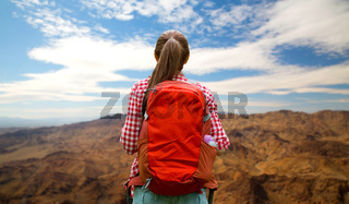 woman with backpack over grand canyon hills