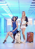 Two young women and dog border collie with suitcases