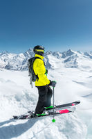 A freerider skier in complete outfit stands on a glacier in the North Caucasus against the background of the Caucasian snow-capped mountains
