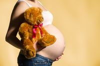 pregnant woman, expectant mother on yellow background, close-up of pregnant belly