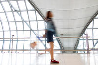 A woman walking in motion blur on white corridor with large windows. Blurred people walking in a modern building. Abstract image of traveler in the lobby.