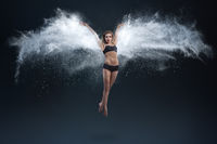 Young woman with powder wings over dark background