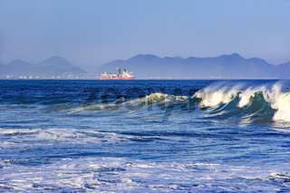 Wave on the beach with ship and hills in the background
