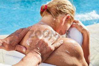 Mann reibt Sonnencreme auf Rücken