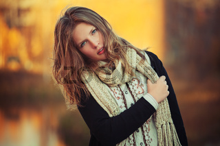 Young fashion girl in black cardigan and knitted scarf walking outdoor