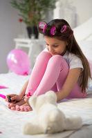 Little girl doing her pedicure.
