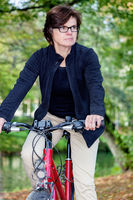 Woman riding a bicycle in autumn park