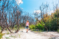 Female walking through burnt bushland that has not regenerated