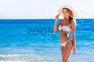 Smiling woman in sunhat on sea beach