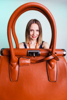 Woman holding brown leather handbag.