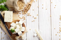 Soy Bean curd tofu in wooden bowl and in hemp sack on white wooden kitchen table. Non-dairy alternative substitute for cheese. Place for text