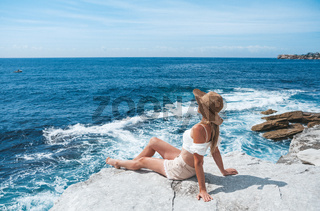 Woman basking in the sun sunbaking by the ocean
