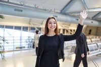 Junge Geschäftsfrau beim Winken im Flughafen