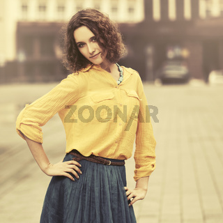 Happy young fashion woman in yellow shirt walking in city street