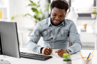 businessman with headphones and papers at office