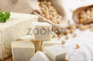 Soy Bean curd tofu on cutting board and in hemp sack on white wooden kitchen table. Non-dairy alternative substitute for cheese