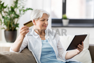 senior woman with tablet pc and credit card