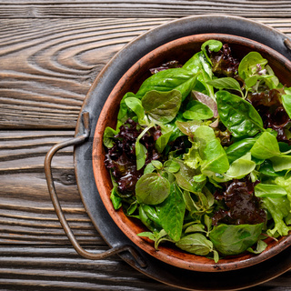 Top view at clay dish with green and violet lettuce, lamb's lettuce salad with oregano flowers on vintage metal tray