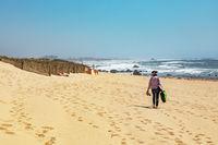 Woman is walking on the sandy beach