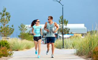 couple in sports clothes running along beach path