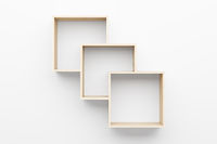 empty wooden shelves on white wall with light from the top
