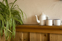Old vintage teapot and two cup of tea on wooden shelf, antique