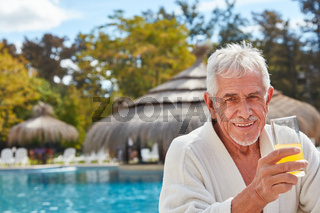 Senior Mann trinkt Orangensaft am Pool