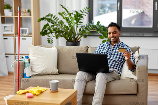 man with laptop shopping online after cleaning